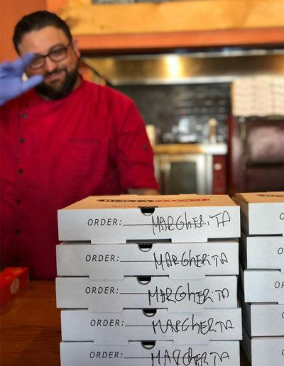 Romanacci Pizza chef prepares boxes for delivery